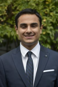 Karan Khosla indian guy in navy blue suit with blue tie with black strips and white shirt and green tree in background